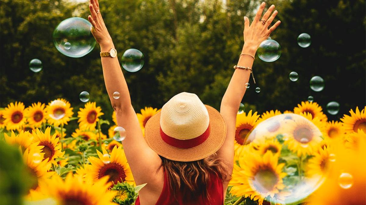 woman wearing hat in flower bed