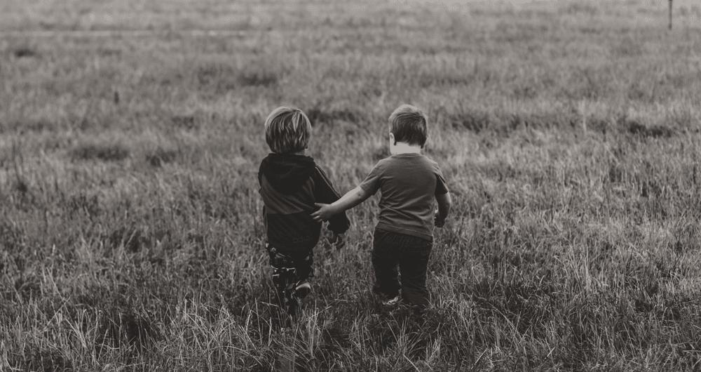 listen money matters - two boys walking in a grassy field