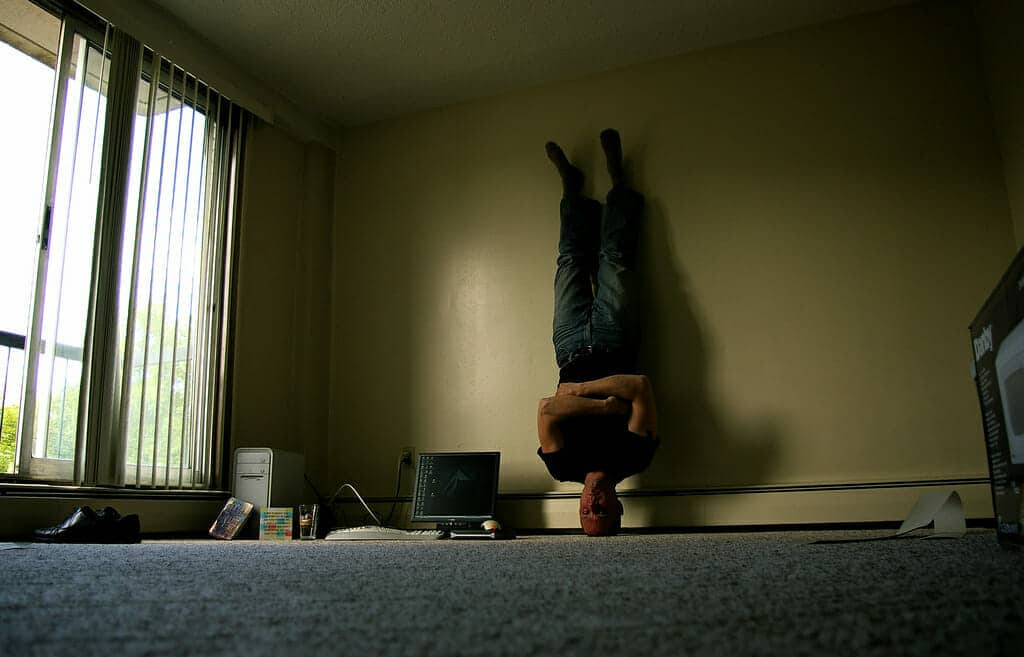 A man is standing on his head in a mostly bare room.
