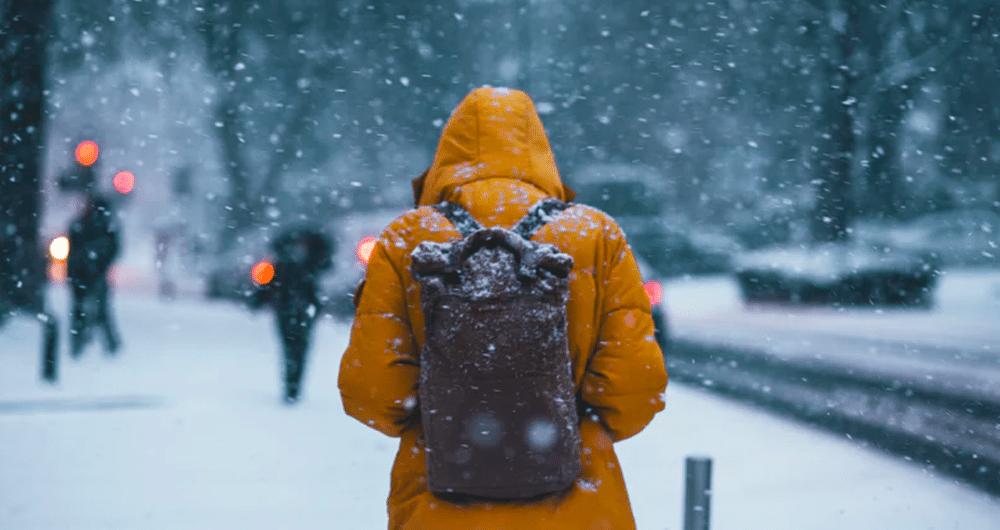 financial-grit person walking in snow wearing jacket