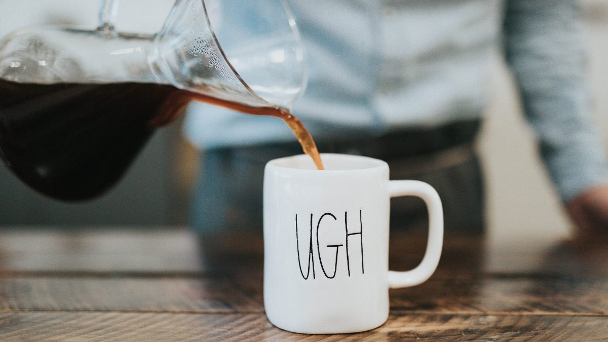 "Coffee being poured into a mug with ""UGH"" written on it."