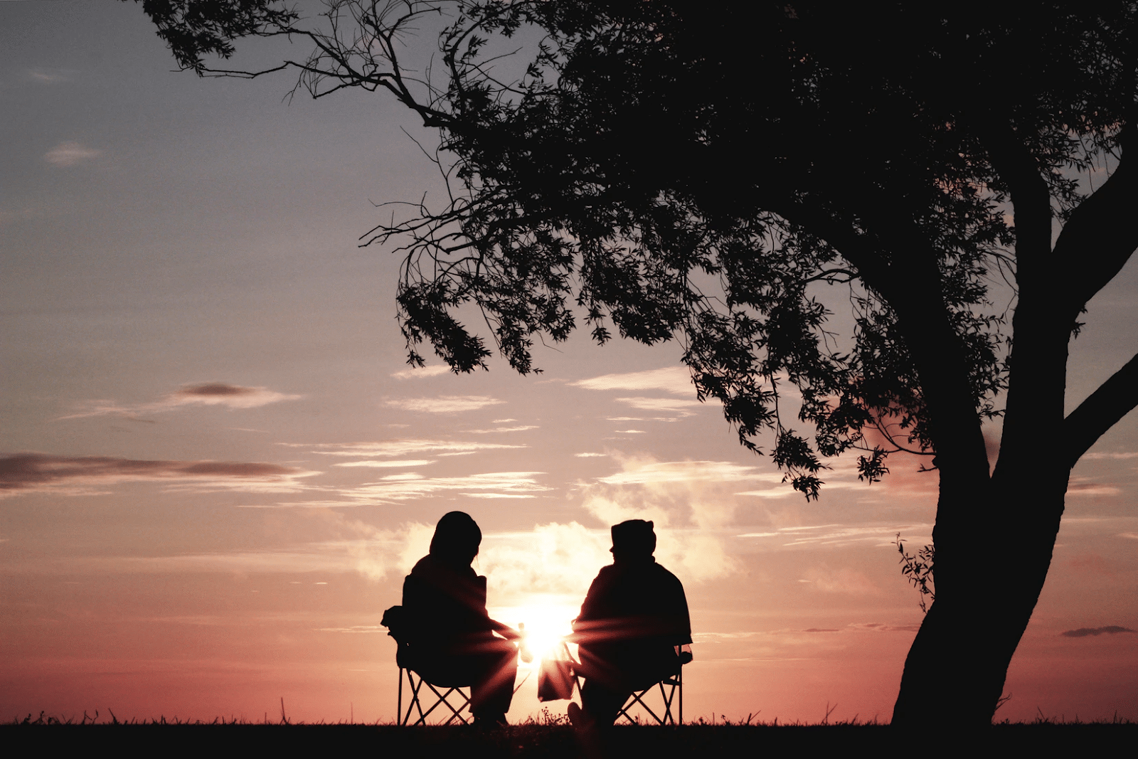 couple sitting in chairs watching sunset