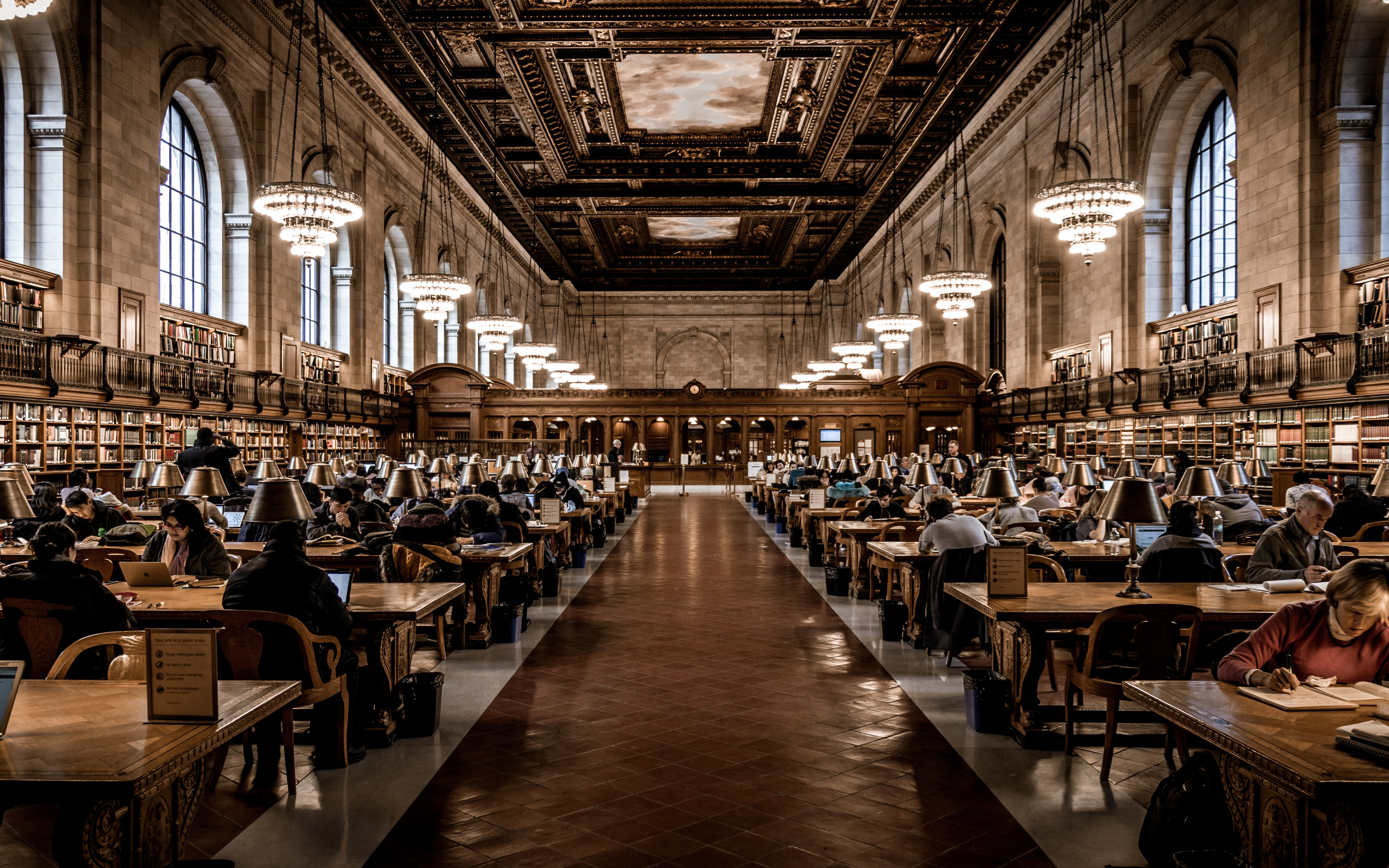 Many people working and reading inside of the New York Public Library.