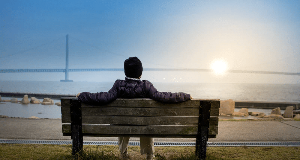 A man sitting on a bench and watching a sunset.