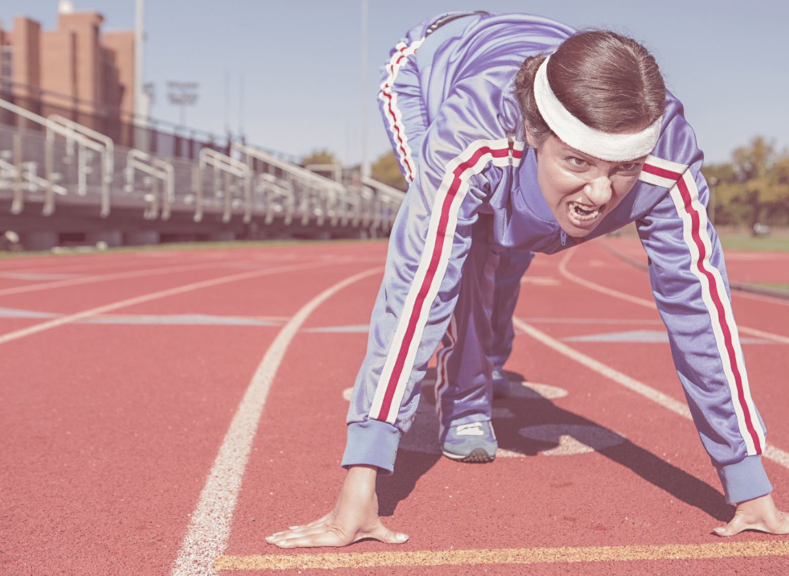 A women at a track starting line, ready to start running.