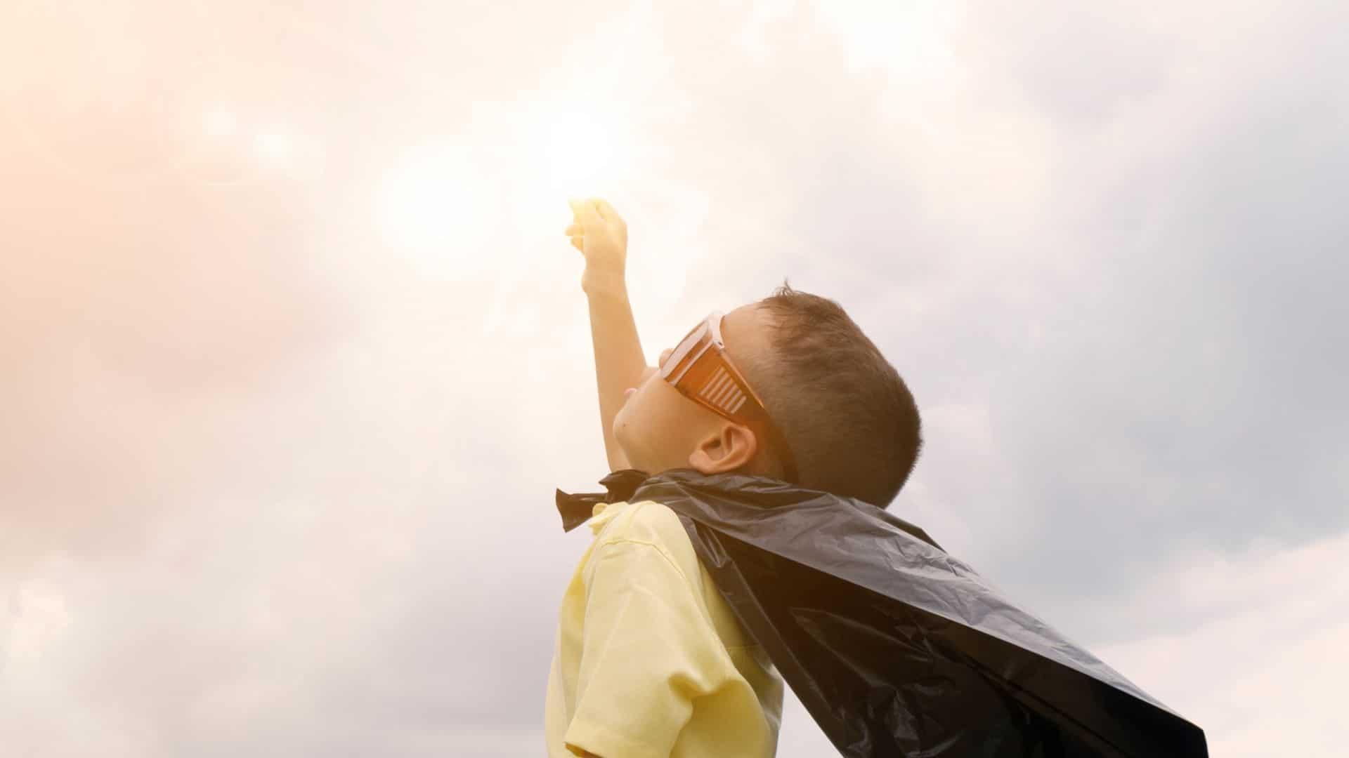 A kid wearing a cape like a superhero.