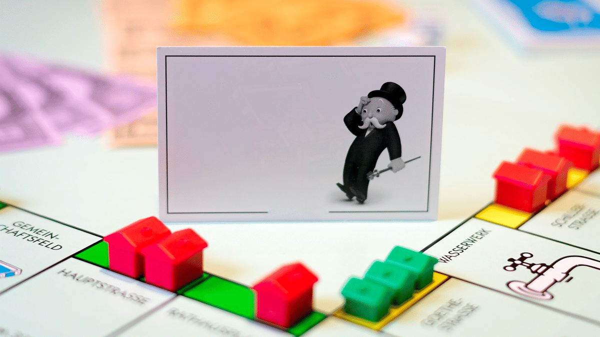 The Monopoly man in shock with multiple houses and apartments on the game board.