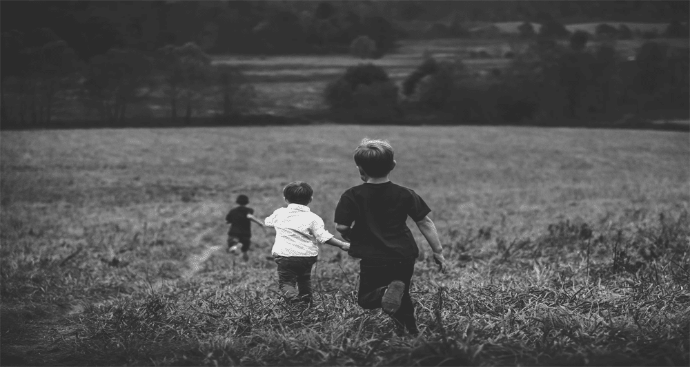 three boys running in a field - making a purchase
